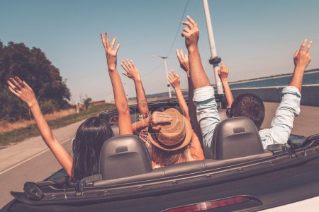 Photo for Rear view of young happy people enjoying road trip in their convertible and raising their arms up - Royalty Free Image