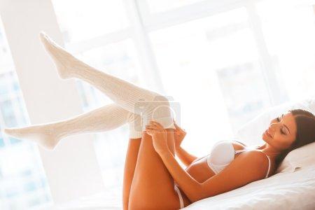 Woman in lingerie taking of her white socks