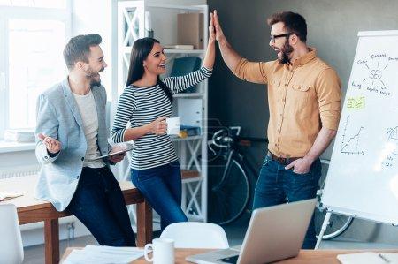 Photo pour Heureux jeune homme debout près de tableau blanc au bureau et en donnant cinq élevés à ses collègues - image libre de droit