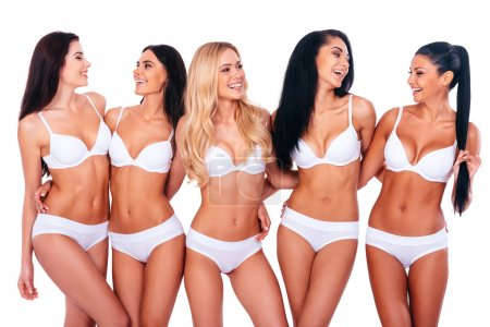 Photo for Carefree beauties. Group of cheerful women in lingerie embracing and looking at each other while standing against white background - Royalty Free Image