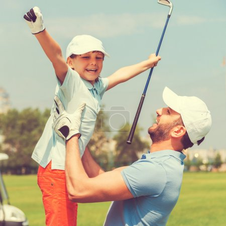 young man picking up son