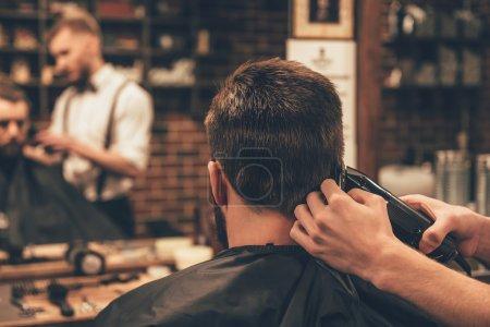 Photo pour Barder travailler avec jeune homme beau dans salon de coiffure - image libre de droit