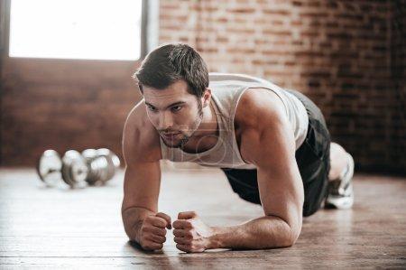 Photo pour La force et la motivation. confiant jeune homme musclé habilement sport sportswear et exercice d'intérieur - image libre de droit