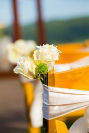 Photo pour Décor de mariage de fleurs blanches liées aux chaises de cérémonie dans ce lieu extérieur . - image libre de droit