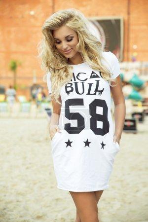 Photo pour Jeune femme blonde belle à la mode posant en plein air dans des vêtements décontractés. Fille avec de longs cheveux bouclés . - image libre de droit
