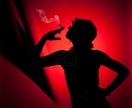 Photo for Silhouette of woman smoking. Profile of woman pulling smoke on red background - Royalty Free Image