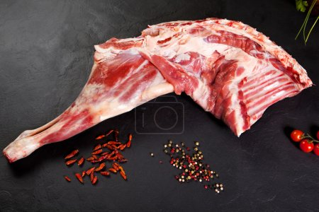 Fresh and raw meat. Leg of lamb uncooked tomato and pepper on black background