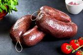 Tepelně neupravené čerstvé krvavé jelito s petrželkou a rajčaty. syrové vepřové maso připravené k vaření