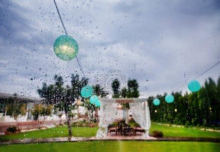 Photo pour Cérémonie extérieure. Décoration des célébrations. Il pleut par la fenêtre. Planificateur de mariage . - image libre de droit