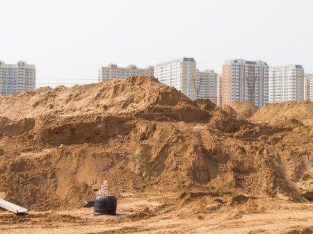 Photo pour Construction d'une nouvelle route avec pose de tuyaux et de gouttières, et beaucoup de sable jaune sur un chantier de construction dans une nouvelle zone - image libre de droit