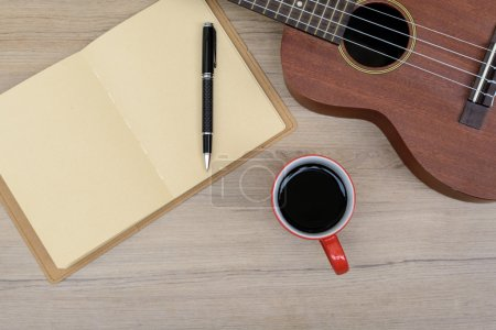 Cup of coffee with ukulele and notebook on wooden table