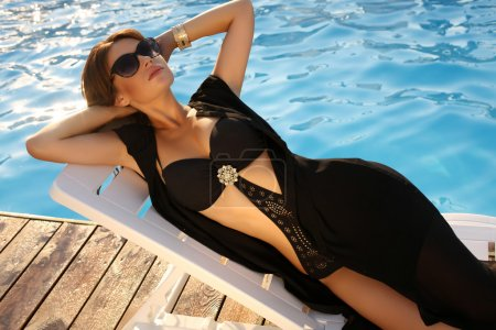 sexy woman with dark hair in black swimsuit relaxing on beach