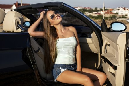 sexy girl with long hair posing in luxury cabriolet