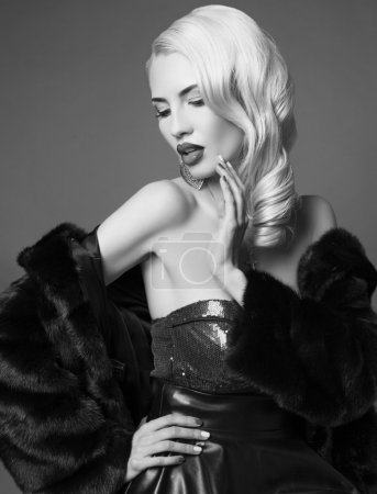 Photo pour Photo de mode noir et blanc de femme sexy aux cheveux blonds dans un élégant manteau en fourrure noire posant en studio - image libre de droit