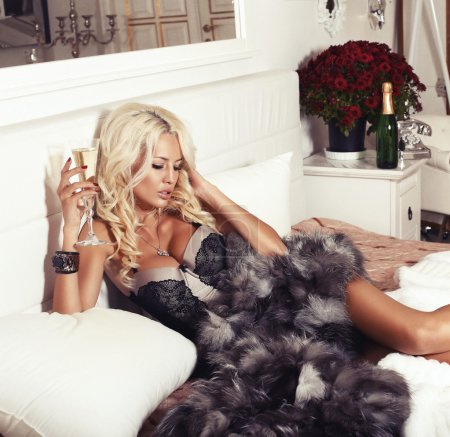 sexy blond woman in lingerie and fur coat lying on bed with champagne