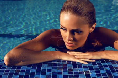 Portrait of sexy blond woman relaxing in swimming pool