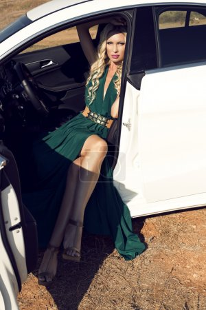 Photo for Fashion outdoor photo of sexy glamour woman with long blond hair in elegant green dress posing in white luxury auto - Royalty Free Image
