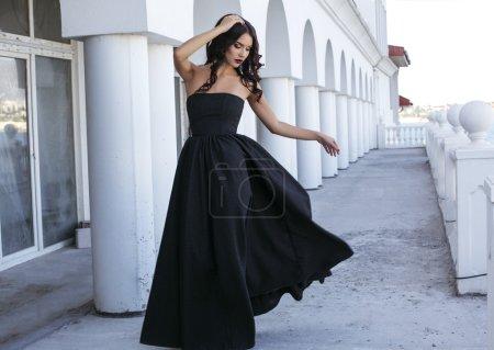 Photo pour Photo extérieure de la mode de la belle femme avec des cheveux noirs bouclé en noir élégant robe walking par parc - image libre de droit