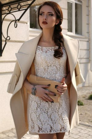 beautiful ladylike woman in elegant wool coat and lace dress