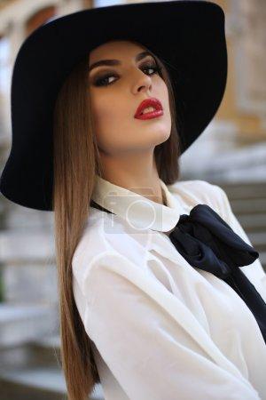 Photo pour Photo de mode en plein air de belle femme comme une dame avec des cheveux noirs droits portant une blouse élégante et un chapeau noir - image libre de droit