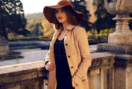 Photo for Fashion outdoor photo of beautiful ladylike woman with dark straight hair wearing elegant coat and felt hat,posing in autumn park - Royalty Free Image
