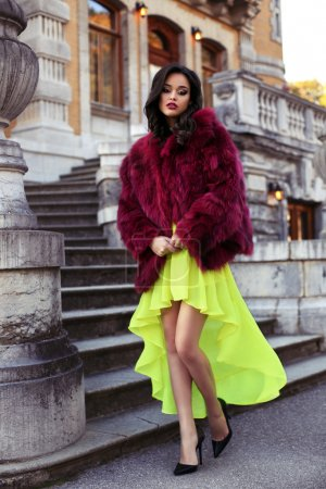 beautiful elegant woman in luxurious fashion red fur coat