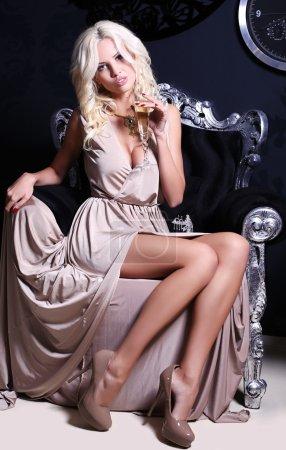 Photo pour Photo intérieur de mode femme sexy glamour avec des cheveux blonds en élégante robe beige tenant le verre de champagne à la main - image libre de droit