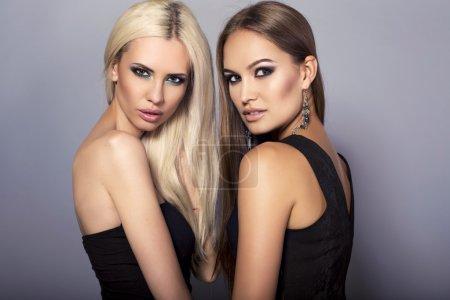 Photo pour Photo studio de mode de deux belles filles sexy avec des cheveux luxueux et un maquillage lumineux - image libre de droit
