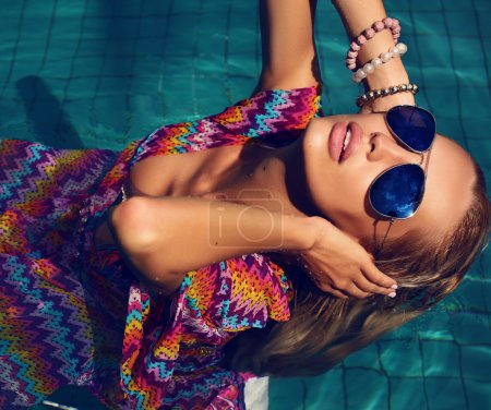 sexy woman with blond hair in sunglasses in swimming pool