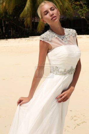 Beautiful bride in wedding dress posing on beautiful island in Thailand