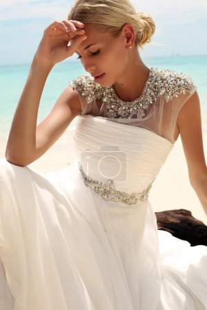 Photo pour Fashion outdoor photo of beautiful woman with blond hair in elegant wedding dress posing on beach in Thailand - image libre de droit