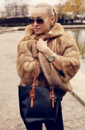 Sexy blond woman in luxurious fur coat and sunglasses