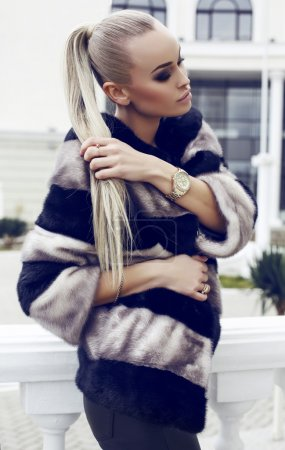 sexy beautiful woman with long straight hair wearing luxurious fur coat