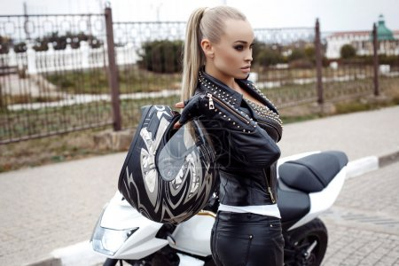 Sexy girl with long blond hair in leather jacket,posing on motorbike