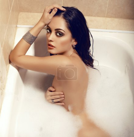 sexy naked woman with dark hair lying in bathtub