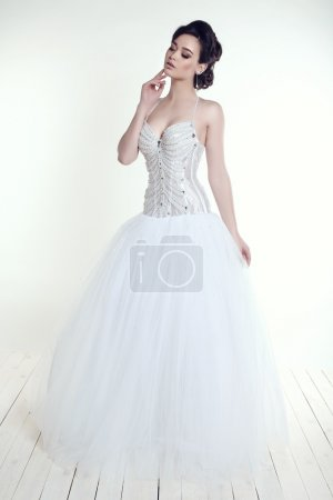 elegant bride with dark hair in luxurious wedding dress
