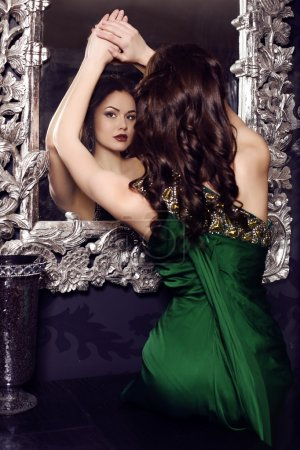 gorgeous woman in elegant green dress posing in luxurious interior