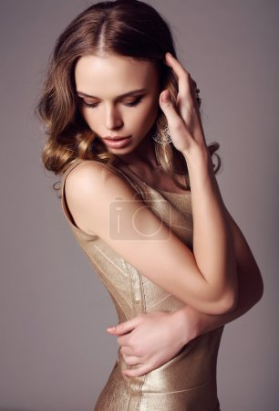 Photo for Fashion stuidio photo of beautiful sensual woman with dark hair in elegant gold dress - Royalty Free Image