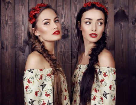 Photo for Fashion studio photo of two beautiful girls with long hair in elegant dresses with print of poppies and flower's headband - Royalty Free Image