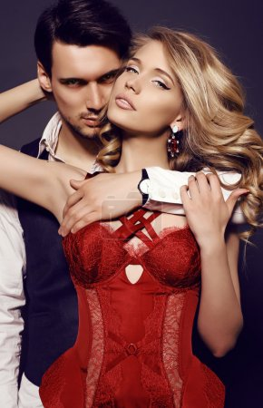 beautiful sensual couple in elegant clothes posing in studio