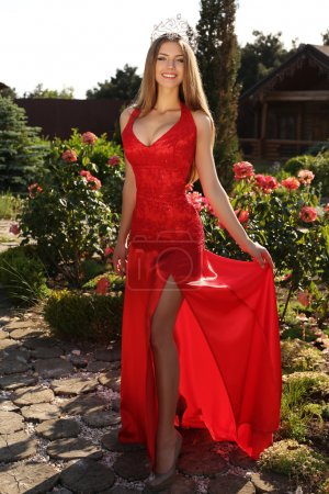 beautiful girl in elegant red dress and luxurious crown