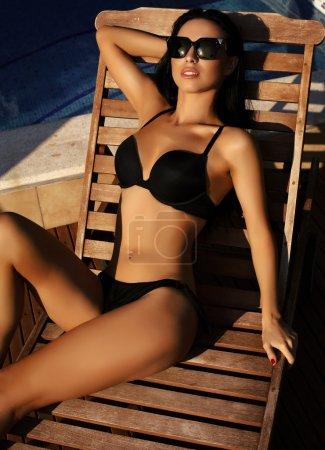 gorgeous sexy woman with dark  hair in elegant black bikini
