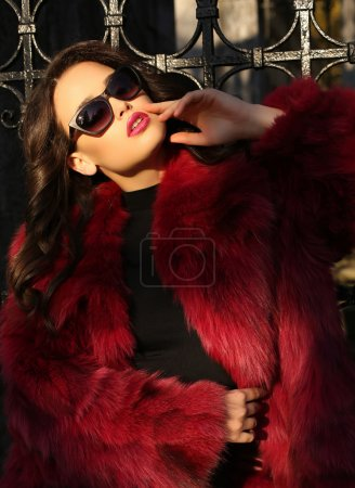 beautiful woman with dark hair wearing luxurious fur coat