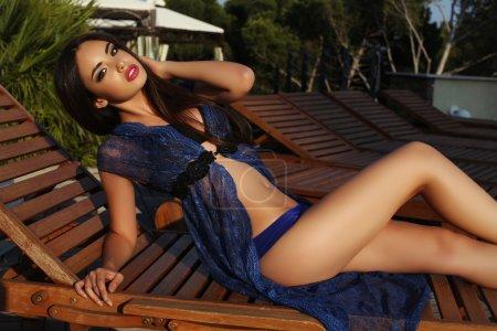 Photo for Fashion outdoor photo of beautiful sensual woman with dark hair wearing elegant bikini and lace robe posing beside swimming pool - Royalty Free Image