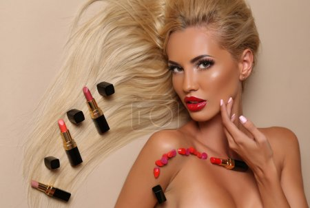 Sensual woman with blond hair with posing with a lot of lipsticks