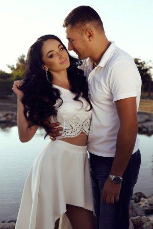 beautiful sensual couple in elegant clothes posing in summer park