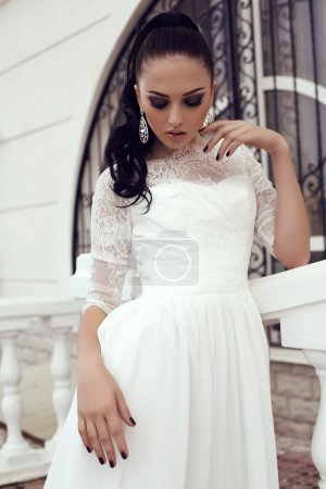 young woman with long dark hair in luxurious lace wedding dress