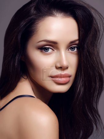 Woman with dark hair and charming smile, with perfect glowing skin
