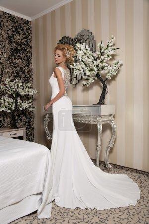 Photo pour Photo studio de mode de magnifique mariée aux cheveux blonds, en robe de mariée luxueuse avec bijou, posant dans la chambre décorée - image libre de droit
