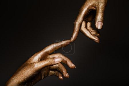 Photo pour Belles mains mans en peinture dorée sur fond noir gros plan - image libre de droit